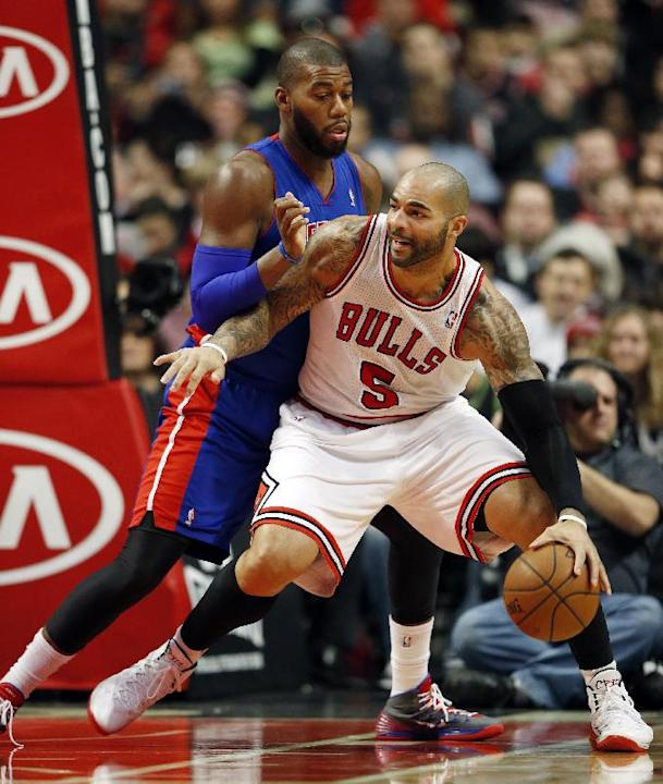 Chicago Bulls forward Carlos Boozer (5) looks for an opening against Detroit Pistons forward Greg Monroe during the first half of an NBA basketball game in Chicago, Saturday, Dec. 7, 2013