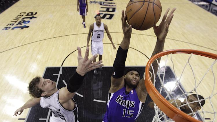 Sacramento Kings' DeMarcus Cousins (15) scores between San Antonio Spurs defenders Tiago Splitter, left, and Tim Duncan, right, during the first half of an NBA basketball game on Friday, March 1, 2013, in San Antonio. (AP Photo/Eric Gay)