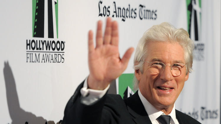 Richard Gere, recipient of the Hollywood Career Achievement Award, waves to photographers at the 16th Annual Hollywood Film Awards Gala on Monday, Oct. 22, 2012, in Beverly Hills, Calif. (Photo by Chris Pizzello/Invision/AP)
