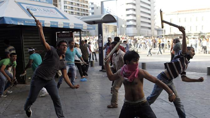 Muslim immigrants living in Greece throw objects at riot police during a protest against a film produced in the U.S. that they say insults the Prophet Muhammad, in Athens, Sun. 23, 2012.  The protesters tried to march to the U.S. Embassy,  but riot police blocked all exits from the square and used tear gas to disperse the protesters. It is the first such protest against the film by Muslims in Greece.(AP Photo/Kostas Tsironis)