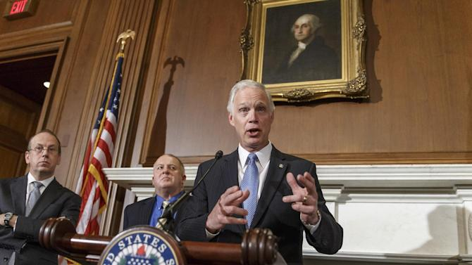 FILE - In this Jan. 6, 2014 file photo, Sen. Ron Johnson, R-Wis., joined by attorneys Paul D. Clement, far left, and Rick Esenberg, second from left, announces that he has filed a lawsuit to block the federal government from helping to pay for health care coverage for members of Congress and their staffs during a news conference on Capitol Hill in Washington. A federal judge will hear arguments this week on whether to toss a U.S. senator's lawsuit challenging rules that force congressional members and their staffs to obtain government-subsidized health insurance through small business exchanges. Johnson contends that senators, representatives and their employees aren't eligible for the exchanges under the federal health care law because they work for a government that employs millions. He also argues that premium subsidies that congressional members and staffers receive will foster resentment among his constituents. (AP Photo/J. Scott Applewhite, File)