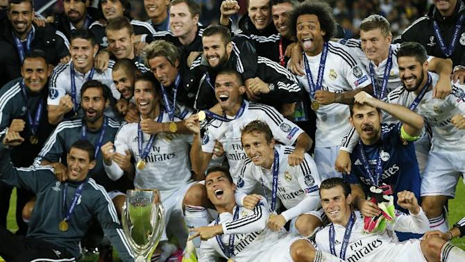 Real Madrid players pose with the trophy after winning the UEFA Super Cup soccer match between Real Madrid and Sevilla in Cardiff City Stadium, in Cardiff, Wales, Tuesday, Aug. 12, 2014. (AP Photo/Alastair Grant)