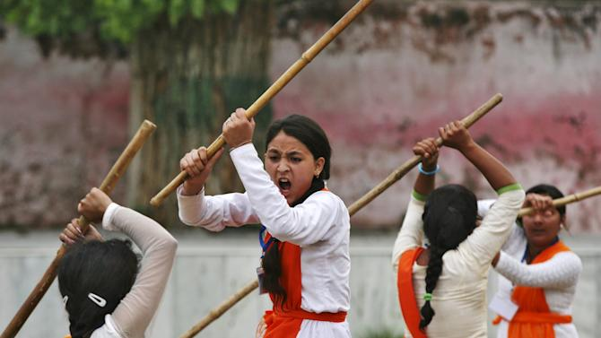 School girls wield bamboo sticks during an event held to demonstrate self-defence skills as part of a camp organized by the Vishwa Hindu Parishad (VHP), a Hindu group, in Jammu