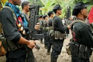 Members of the rebel New People's Army stand in formation during the 40th anniversary celebrations of the Communist Party of the Philippines inside a remote camp in Davao, in the southern Island of Mindanao. Philippine communist guerrillas have killed 11 soldiers and a civilian in one of their most audacious attacks in recent years, the military said