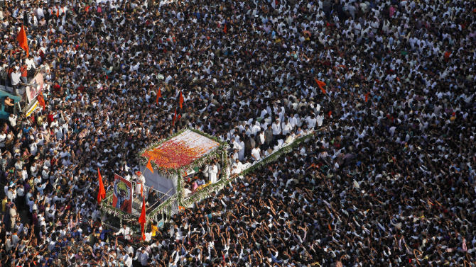 Indian mourners gather beside a truck carrying the body of Hindu hardline Shiv Sena party leader Bal Thackeray during his funeral in Mumbai, India, Sunday, Nov. 18, 2012. Hundreds of thousands of supporters have filled the streets of Mumbai for the funeral of Thackeray, a Hindu extremist leader linked to waves of mob violence against Muslims and migrant workers in India. Thackeray died Saturday after an illness of several weeks. He was 86. (AP Photo/Rajanish Kakade)