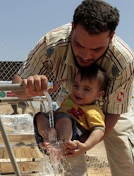 A Syrian refugee man washes a baby's feet at the Zaatari refugee camp in the Jordanian city of Mafraq, near the border with Syria, on August 6. A charity that cares for thousands of Syrians who fled violence said last week that the first official camp to house the refugees in neighbouring Jordan falls short of international standards