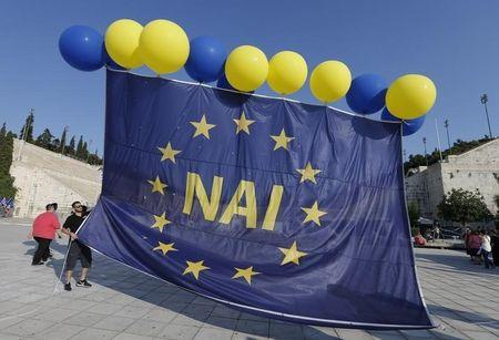 Men prepare large EU flag printed with the word 'yes' prior to the pro-Euro rally at Panathenean stadium in Athens