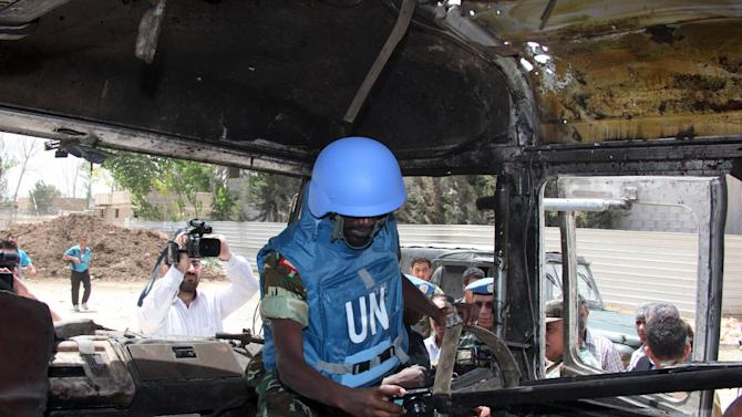 A U.N. observer takes pictures of a military bus that was damaged by a roadside bomb, at al-Bahdaliyah area, near Damascus, Syria, Wednesday, May 23, 2012. Syria's uprising began in March 2011 with mostly peaceful calls for reform, but the government's brutal crackdown on dissent led many in the opposition to take up arms. The U.N. estimates more than 9,000 people have been killed as the conflict spirals toward civil war. (AP Photo/Bassem Tellawi)