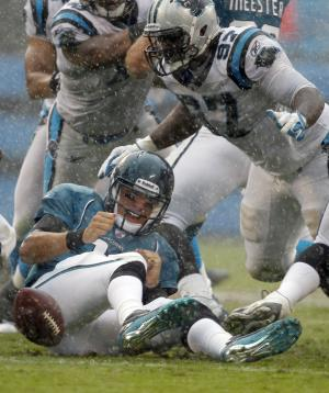 In the rain, Jacksonville Jaguars' Blaine Gabbert (11) fumbles the ball as Carolina Panthers' Terrell McClain (97) defends during the second quarter of an NFL football game in Charlotte, N.C., Sunday, Sept. 25, 2011. The Panthers were ruled offside on the play. (AP Photo/Bob Leverone)