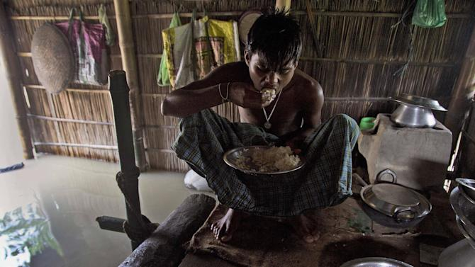 A boy eats rice inside his house partially submerged in flood waters at Gagolmari village 85 kilometers (53 miles) east of Gauhati, India, Wednesday, Sept. 2, 2015. Monsoon floods have inundated hundreds of villages across the northeast Indian state of Assam, killing at several people and forcing some 800,000 people to leave their homes. (AP Photo/Anupam Nath)