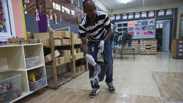 Angesom Solomon, a 28-year-old African migrant from Eritrea, cleans classroom at a school in Tel Aviv