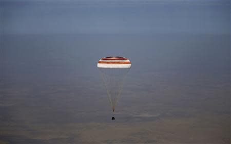 A Soyuz spacecraft carrying Russian cosmonauts Vinogradov and Misurkin and NASA astronaut Cassidy descends beneath a parachute just before landing near Zhezkazgan