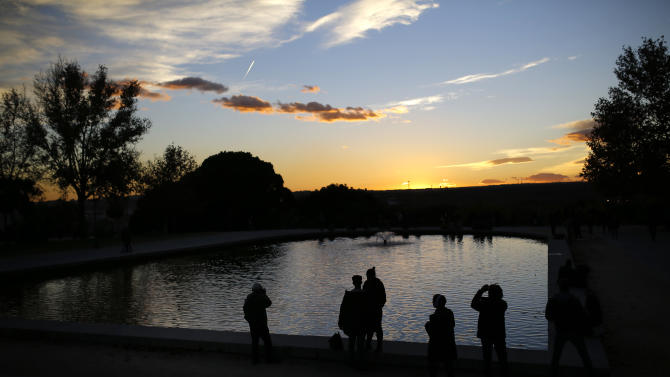 People take photographs at the Temple of Debod park as the sun sets in Madrid, Thursday, Nov. 26, 2015. The park is frequented mostly by locals but also attracts tourists due to its view of the city at sunset. (AP Photo/Francisco Seco)