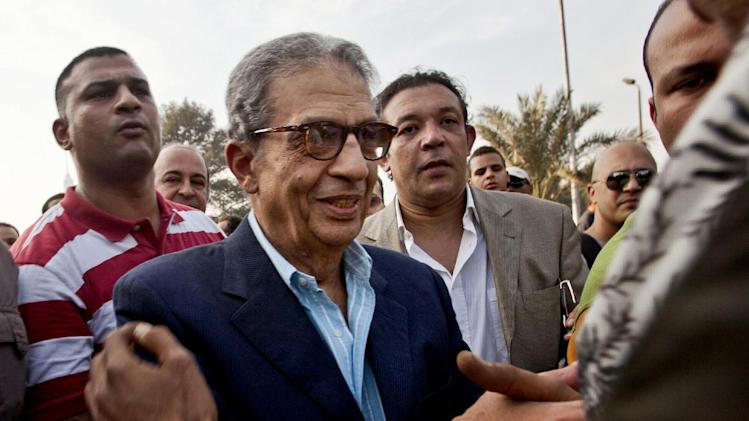 FILE - In this Friday, Nov. 30, 2012 file photo, former foreign minister and presidential candidate Amr Moussa, center, greets supporters as he arrives to Tahrir Square to join other liberal and secular parties for a major protest against Egyptian President Mohammed Morsi's latest decrees granting himself almost complete powers and allowing a rushed constitution to be presented for a vote. An Egyptian official says the country's top prosecutor has ordered an investigation into accusations against opposition leaders, Mohammed ElBaradei, Amr Moussa, and Hamdeen Sabahi, of incitement to overthrow the regime. (AP Photo/Thomas Hartwell, File)