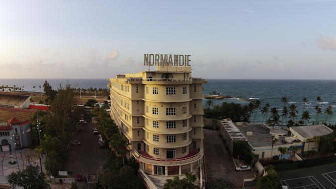 In this Wednesday, July 29, 2015 photo, the Normandie hotel sits abandoned in San Juan, Puerto Rico. Closed since 2008 was originally opened on October 10, 1942 and It's design was inspired by the ocean liner SS Normandie. On August 29, 1980 was declared a national historic site and added to the National Register of Historic Places by the U.S. Interior Department's Heritage Conservation and Recreation Service. (AP Photo/Ricardo Arduengo)