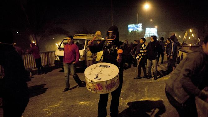 An Egyptian protester wearing a tear gas mask plays the drums to encourage fellow protesters during clashes with security forces following an-anti president Mohammed Morsi protest near the Qasr al-Kobba palace, one of the president's secondary residences, in Cairo, Egypt, Friday, Feb. 15, 2013. Several thousand hard-line Islamists rallied in Cairo on Friday against a recent wave of violent anti-government protests, while liberal activists staged a smaller demonstration across town to call for accountability and justice from the country's leaders. (AP Photo/Nasser Nasser)