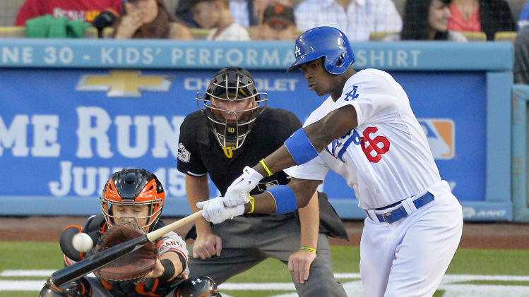 Los Angeles Dodgers' Yasiel Puig, right, hits a solo home run as San Francisco Giants catcher Buster Posey, left, catches and home pate umpire Lance Barksdale watches during the first inning of their baseball game, Monday, June 24, 2013, in Los Angeles. (AP Photo/Mark J. Terrill)