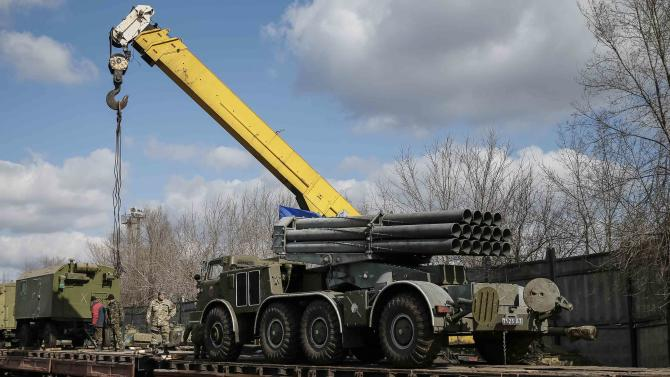 Multiple rocket launcher system belonging to the Ukrainian armed forces is driven onto a wagon of a cargo train at a train station in Artemivsk
