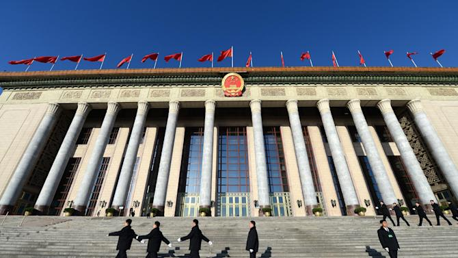 File picture shows security personnel marching past the Great Hall of the People in Beijing on March 13, 2014