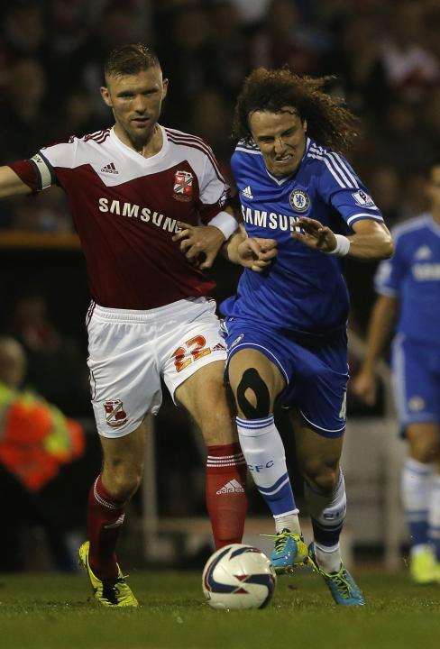 Swindon Town's Ward challenges Chelsea's Luiz during their English League Cup soccer match at the County Ground in Swindon