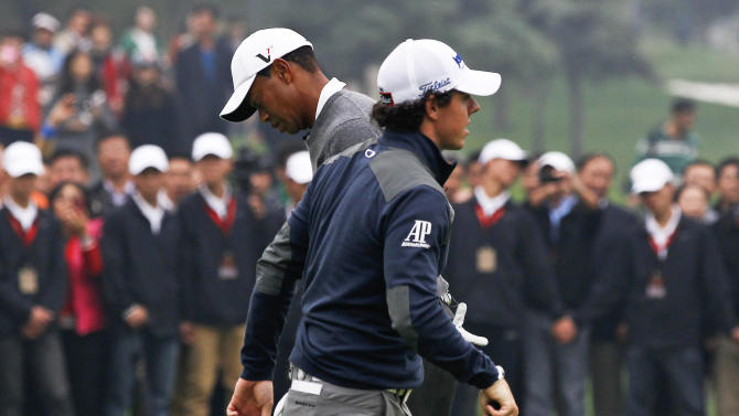 FILE - In this Oct. 29, 2012 photo, Tiger Woods of the United States, back, and Rory McIlroy of Northern Ireland, front, play on the 10th green during their 18-hole medal-match at the Lake Jinsha Golf Club in Zhengzhou, in central China's Henan province. The world's two top golfers are meeting more and more often on the course, but neither No. 1-ranked Rory McIlroy or Tiger Woods are ready to call it a rivalry. The pair, set to meet at the Abu Dhabi Golf Championship, starting from Jan. 17, 2013,  have established a blossoming relationship since playing together for the first three rounds of last year's tournament and have expressed a mutual respect for one another's game. (AP Photo/Alexander F. Yuan, File)