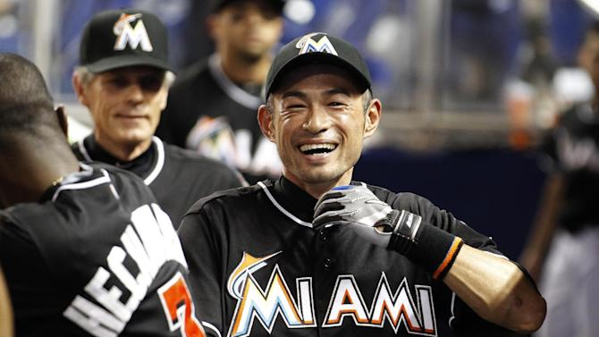 Miami Marlins' Ichiro Suzuki is cheered by teammates before the Marlins met the Baltimore Orioles in a baseball game in Miami, Saturday, May 23, 2015. (AP Photo/Joe Skipper)