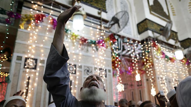In this Tuesday, June 4, 2013 photo, a man prays at the shrine of Sayyeda Zeinab, in Cairo, Egypt. Egypt's roughly 15 million Sufi Muslims say their places of worship are under threat by rising radicalism. They say that since the country's 2011 uprising that toppled longtime autocrat Hosni Mubarak, shrines held sacred to them have been attacked by hardliners who deem them heretical and idolatrous. Egyptians celebrate Moulid, which commemorates the birth of Muslim Prophet Mohammed's granddaughter, Zeinab, by performing ritual dances and prayers and having fun with their families. (AP Photo/Hassan Ammar)