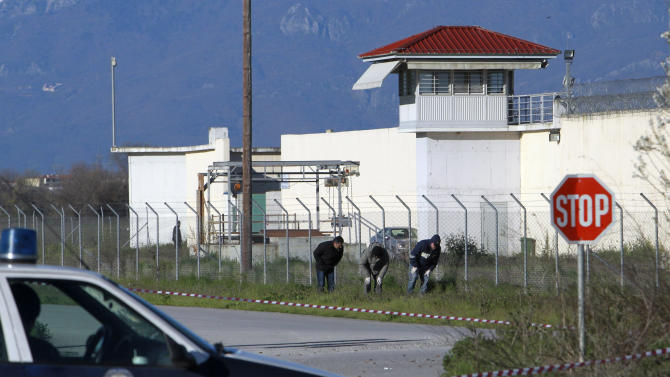 Police officers  search for evidence   in front of a prison  near the city of Trikala, central Greece, on Saturday, March 23, 2013. At least 11 inmates escaped from the Greek prison after gunmen brazenly attacked the site with grenades and automatic weapons, kicking off a nightlong standoff between police and prisoners. Two guards were injured, one of them seriously. The attack was the latest dramatic incident at Greek prisons, which are suffering from serious overcrowding and staff shortages as the country struggles through financial crisis and a recession that started in late 2008.(AP Photo/Nikolas Giakoumidis)