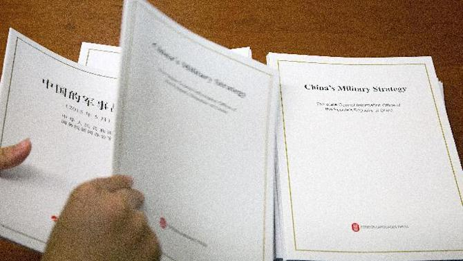 A journalist picks up copies of a report on China's Military Strategy distributed by Defense Ministry during a press conference at the State Council Information Office in Beijing, China, Tuesday, May 26, 2015. China's military on Tuesday compared its controversial island-building in the South China Sea to ordinary construction such as road-building going on elsewhere in the country, trying to deflect criticism over an issue seen as inflaming tensions in the region. (AP Photo/Andy Wong)