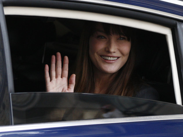 "FILE - In this May 15, 2012 file photo, Carla Bruni-Sarkozy, wife of outgoing President Nicolas Sarkozy, waves from a car as they leave the Elysee Palace after the presidential handover ceremony. Carla Bruni-Sarkozy has said Monday, Nov. 26, 2012 she supports the French Socialist's plans for gay marriage, and disagrees with her Conservative husband Nicolas Sarkozy. In an interview in the December issue of Paris Vogue, the 44-year-old former supermodel and singer said: ""I'm rather in favor because I have a lot of friends - men and women -who are in this situation and I see nothing unstable or perverse in homoparental families."" (AP Photo/Michel Euler, File)"