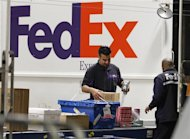 <p>Handlers scan and affix a courier route label onto packages moving down the belt at the Marina Del Rey, California FedEx station December 12, 2011. REUTERS/Fred Prouser</p>