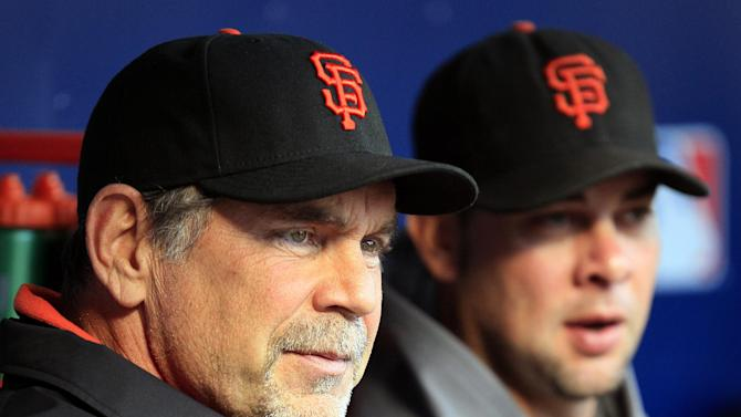 San Francisco Giants manager Bruce Bochy, left, watches from the dugout in the first inning of Game 4 of the National League division baseball series against the Cincinnati Reds, Wednesday, Oct. 10, 2012, in Cincinnati. (AP Photo/Al Behrman)