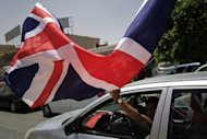A Libyan man waves the Union Jack as he drives through the Libyan rebel-stronghold city of Benghazi. Libyan rebels seized two localities near the Tunisian border on Thursday as part of their pre-Ramadan offensive aimed at unseating strongman Moamer Kadhafi, an AFP correspondent said