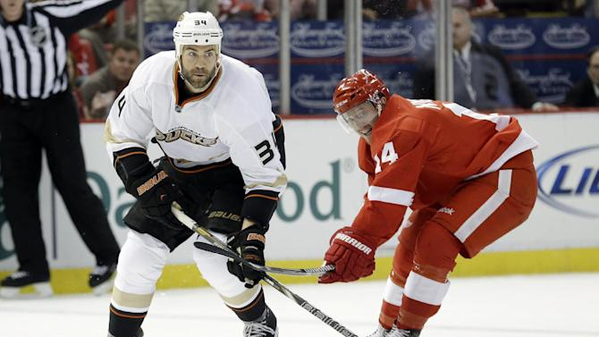 Detroit Red Wings center Gustav Nyquist (14), of Sweden, tries to slow Anaheim Ducks center Daniel Winnik (34) in the first period in Game 6 of a first-round NHL hockey Stanley Cup playoff series in Detroit, Friday, May 10, 2013. (AP Photo/Paul Sancya)