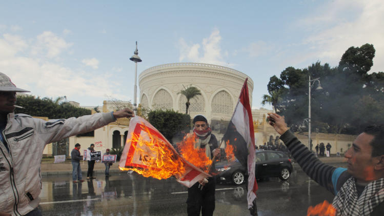 "Egyptian protesters burn an Arabic banner reading ""Hamas, brotherhood, Qatar and America, are Egyptian enemies,"" in front of the presidential palace in Cairo, Egypt, Friday, Feb. 1, 2013. Thousands of Egyptians marched across the country, chanting against the rule of the Islamist President Mohammed Morsi, in a fresh wave of protests Friday, even as cracks appeared in the ranks of the opposition after its political leaders met for the first time with the rival Muslim Brotherhood. (AP Photo/Amr Nabil)"