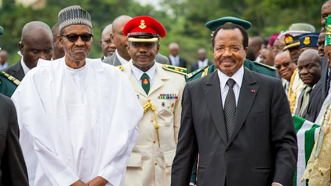 Nigeria's President Muhammadu Buhari(L) walks with Cameroon's President Paul Biya(R) as he arrives on an official visit to Cameroon in Yaounde