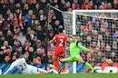 Swansea midfielder Gylfi Sigurdsson (L) slides the ball past Liverpool goalkeeper Simon Mignolet (R) to score the winning goalin the English Premier League match at Anfield in Liverpool, north-west England on January 21, 2017