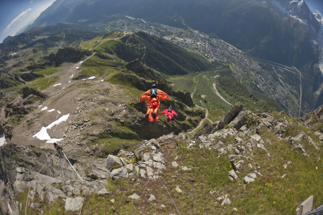 In this photo dated July 21st, 2012, two base jumpers wearing wingsuits jump from the Brevent needle above Chamonix in the French Alps. For nearly two months, daredevils in skin-tight suits with batwing sleeves and a flap between their legs hurled themselves off the Brevent cliff, soaring through the Alpine skies. Last week, tragedy struck: A Norwegian wingsuit flyer was killed when his parachute failed to open. The next day, the mayor of Chamonix-Mont Blanc banned wingsuits. The decision has triggered a debate about how to weigh the dangers of extreme sport against the passion of the thrill-seekers the Alpine town has famously encouraged.. (AP Photo/Cyril Duval)
