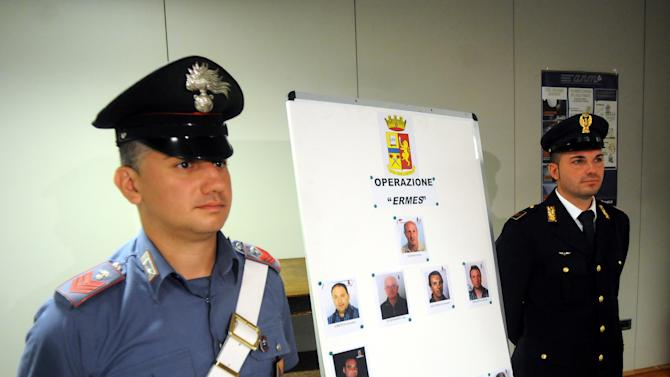 An Italian Carabinieri paramilitary police officer and a police officer stand next to mug shots of 11 men suspected of helping Matteo Messina Denaro during a press conference in Palermo, Italy, Monday, Aug. 3, 2015. Italian investigators say they've discovered how the No. 1 Cosa Nostra fugitive communicates with henchmen using written messages buried in dirt or hidden under boulders on Sicilian sheep ranches: in pre-dawn raids Monday in western Sicily, police arrested 11 men suspected of helping Matteo Messina Denaro stay in command despite being on the run since 1993. (AP Photo/Alessandro Fucarini)