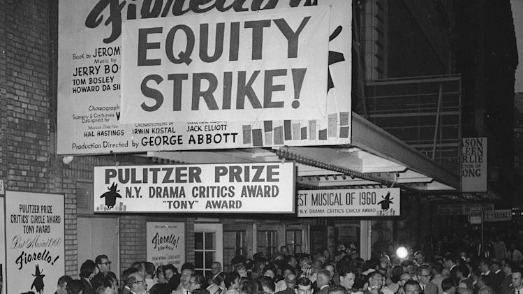 FILE - This June 2, 1960 file photo shows members of the cast and spectators crowding around the entrance to the New York's Broadhurst Theater on 44th Street.  Producers of 22 Broadway shows shut down their productions in retaliation for actors walkout of a single show the night before.  Actors' Equity contract expired at midnight on May 31 without a settlement of dispute with producers.  The Actors' Equity Association, which has begun a yearlong celebration of its centennial, will get a Special Tony in recognition of their work negotiating wages, working conditions and benefits for stage performers and crew members. (AP Photo/Matty Zimmerman, file)