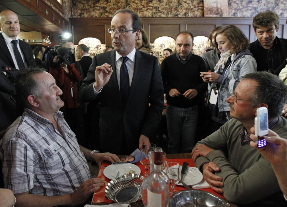 Socialist Party candidate for the presidential election Francois Hollande, center, talks to residents in a restaurant before having a lunch in Tulle, central France, Sunday, May 6, 2012.  (AP Photo/Christophe Ena)