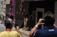 Passersby take snapshots of the facade of the Kiss nightclub where a blaze killed more than 230 people, on January 28, 2013, in Santa Maria, southern Brazil
