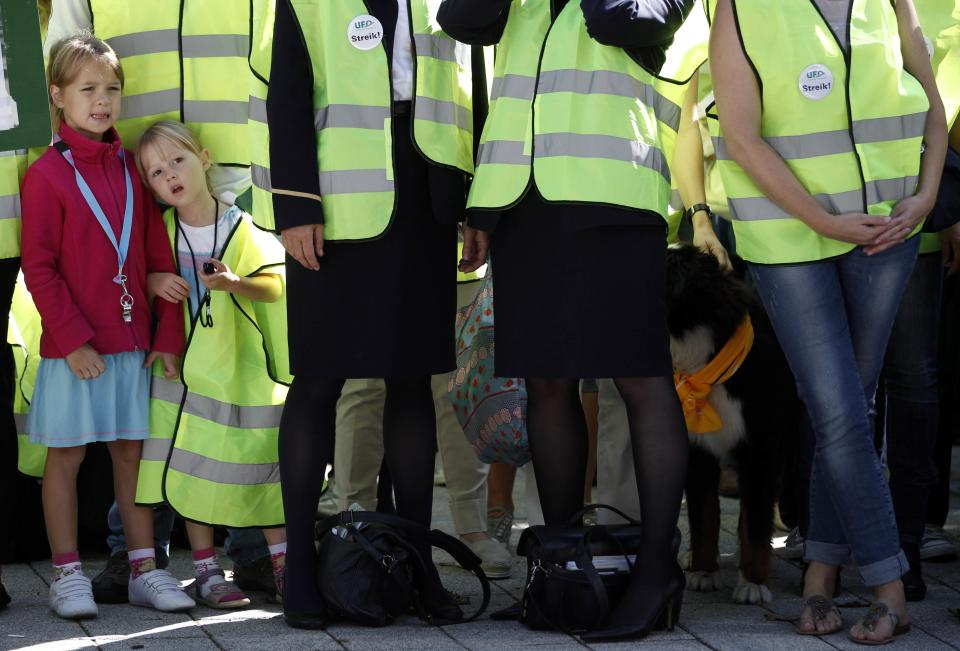 Children of Lufthansa cabin crew members watch a demonstration as flight attendants of German Lufthansa airline went on an 24-hour-strike for higher wages at the airport in Munich, southern Germany, on Friday, Sept. 7, 2012. (AP Photo/Matthias Schrader)