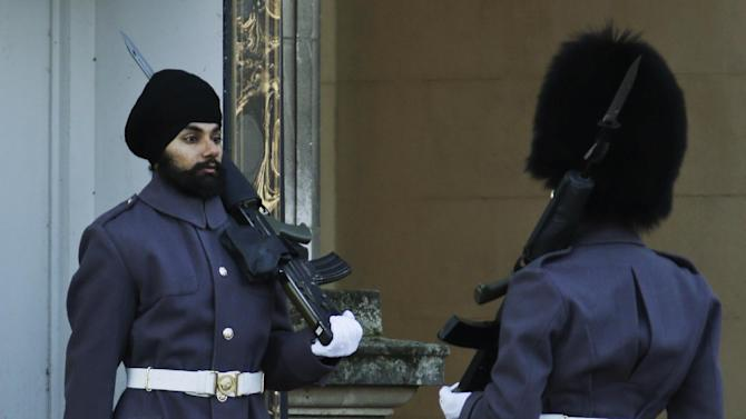 An officer, right, checks Jatinderpal Singh Bhullar, 25, a Sikh soldier with the Scots Guards, performs guarding duties outside Buckingham Palace in central London, Tuesday, Dec. 11, 2012. becoming the first guardsman to parade wearing a turban instead of the famous bearskin. Other Sikhs have taken part in guarding the queen's palace in the past but they wore traditional bearskin hats, rather than turbans. (AP Photo/Lefteris Pitarakis)
