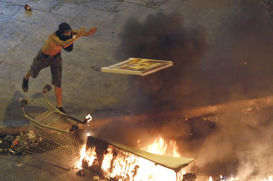 A protestor throws a panel top of a burning barricade during a demonstration in Athens Tuesday evening June 28, 2011. Greece's beleaguered government is bracing for a 48-hour general strike as lawmakers debate a new round of austerity reforms designed to win the country additional rescue loans needed avoid bankruptcy.  (AP Photo/Dimitri Messinis)