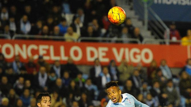 Celta Vigo's Belgian forward Theo Bongonda (R) kicks the ball next to Sporting Gijon's midfielder Jony during the Spanish league football match RC Celta de Vigo vs Real Sporting de Gijon at the Balaidos stadium in Vigo on November 28, 2015