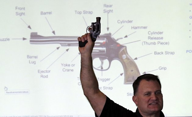 Clark Aposhian, President of Utah Shooting Sport Council, holds a pistol during concealed weapons training for 200 Utah teachers Thursday, Dec. 27, 2012, in West Valley City, Utah. The Utah Shooting S