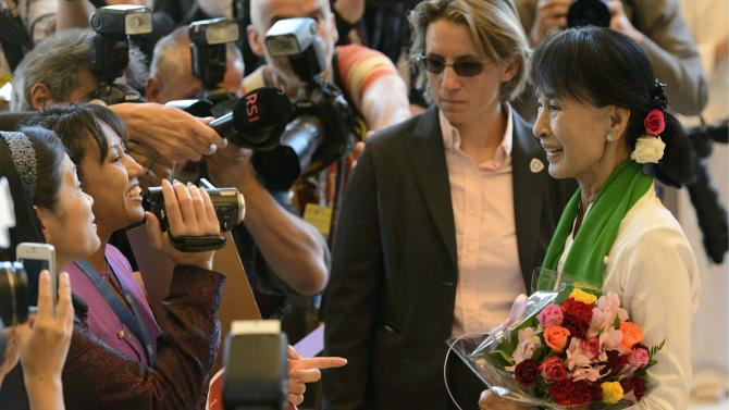 """Myanmar opposition leader Aung San Suu Kyi, right, arrives during the 101st International Labor Organization, ILO, Conference at the European headquarters of the United Nations in Geneva, Switzerland, Thursday, June 14, 2012. Suu Kyi has welcomed steps by the international community to reach out to her country, long isolated because of its military dictatorship. The Nobel laureate says """"the international community is trying very hard to bring my country into it and it's up to our country to respond the right way."""" Suu Kyi arrived in Geneva late Wednesday on her first visit to Europe in 24 years. (AP Photo/Keystone, Laurent Gillieron)"""