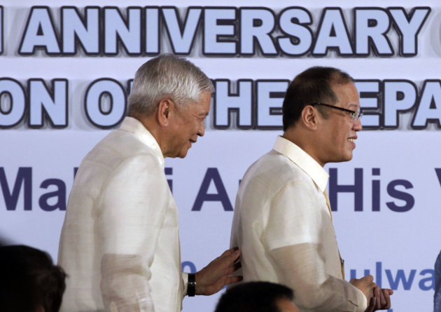 Philippine President Benigno Aquino III, right, leaves the stage followed by Secretary Albert Del Rosario after he delivers his message during the 114th Foundation of the Department of Foreign Affairs