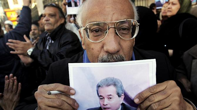 A supporter of Tawfiq Okasha, a popular Egyptian TV presenter, kisses his poster at the Cairo South court in Cairo, Egypt, Tuesday, Jan. 8, 2013. An Egyptian court acquitted Okasha on charges of inciting the killing of the country's new president Mohammed Morsi. (AP Photo/Amr Nabil)